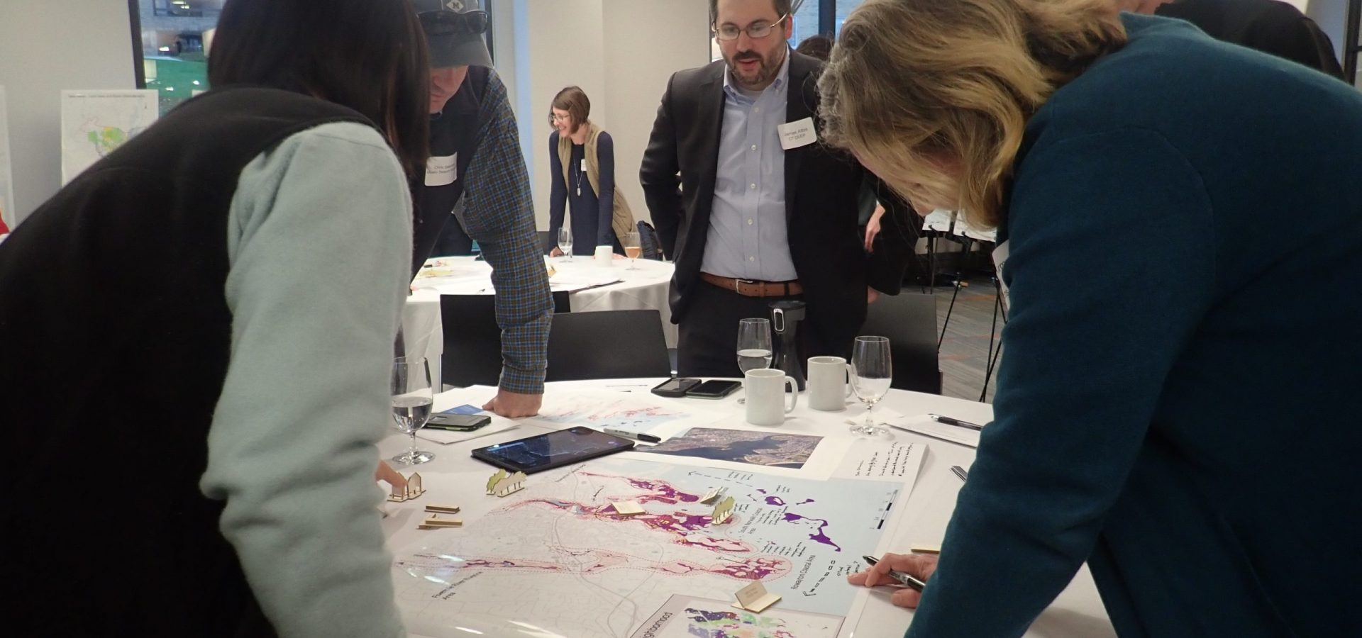 people standing around table looking at map